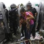 A Honduran migrant mother and child were surrounded by Mexican Federal Police in riot gear.