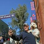 Joe Coen used his phone to snap a few celebratory selfies of himself and his dog Cooper in front of the newly installed championship banner.