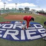 Grounds crew members paint the World Series logo behind home plate at Fenway Park, Sunday, Oct. 21, 2018, in Boston as they prepare for Game 1 of the baseball World Series between the Boston Red Sox and the Los Angeles Dodgers scheduled for Tuesday. (AP Photo/Elise Amendola)