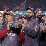 Los Angeles, CA: 10-28-18: Manager Alex Cora (left) hoists the trophy as (left to right) David Price, Rick Porcello, Chris Sale and Eduardo Nunez look on while the Red Sox celebrate their World Series victory. The Boston Red Sox visited the Los Angeles Dodgers in Game Five of the World Series at Dodger Stadium. (Jim Davis/Globe Staff)