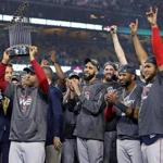 Los Angeles, CA: 10-28-18: Manager Alex Cora hoists the trophy as the Red Sox celebrate their World Series victory. David Price is in the middle. The Boston Red Sox visited the Los Angeles Dodgers in Game Five of the World Series at Dodger Stadium. (Jim Davis/Globe Staff)