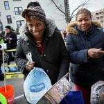 Martine Joseph (left) and Marie Alexia picked up turkeys and grocery packages Saturday at Catholic Charities Yawkey Center.