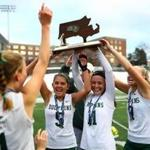 Dennis-Yarmouth field hockey captains hoist their Divison 2 state championship trophy, after defeating Greenfield.