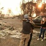 Kimberly Spainhower hugged husband Ryan while daughter Chloe looked on near the burned remains of their home in Paradise, Calif.