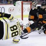 Philadelphia Flyers' Carter Hart, center, and Radko Gudas, right, cannot stop a goal by Boston Bruins' David Pastrnak during the first period of an NHL hockey game, Wednesday, Jan. 16, 2019, in Philadelphia. (AP Photo/Matt Slocum)