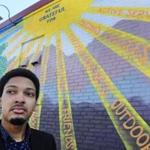Jordan Thompson, 20, is one of 22 men from around the country picked to participate in Barack Obama's My Brother's Keeper summit in Oakland, Calif. He poses in Nashua, N.H., next to a mural near City Hall created by PositiveStreetArt.org.