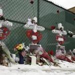 Five crosses set near the Henry Pratt Co. warehouse in Aurora, Ill., on Sunday bore the names of the people who died in a shooting there Friday.