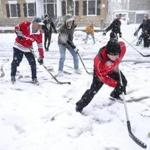 Ware Cady's son, Ware Jr. (right), made a play on the ball during the street hockey game on Chestnut Street on March 10.