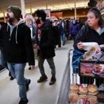 A shopper watched as Jim Carvalho (left) marched with fellow members of the United Food and Commercial Workers Union and their supporters during a rally Sunday at the Stop & Shop in Somerville.