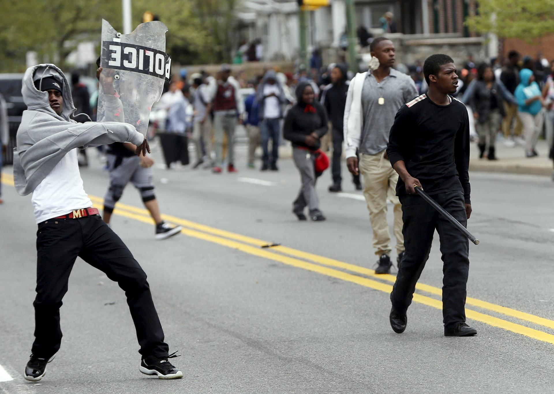 Baltimore police officers in riot gear push protestors back along - Demonstrators Threw Rocks At The Police