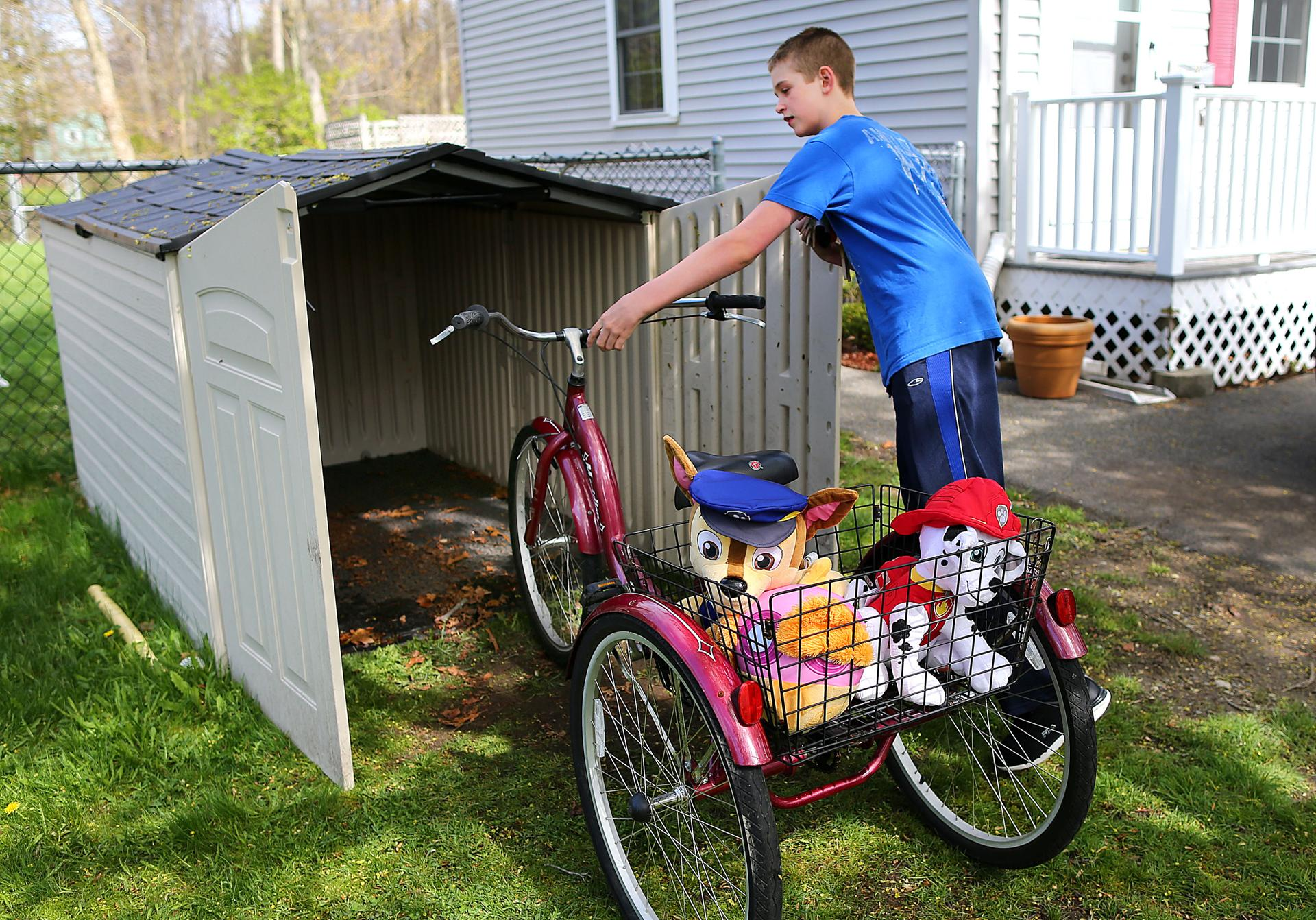 Dillon put his tricycle away in a front yard shed.