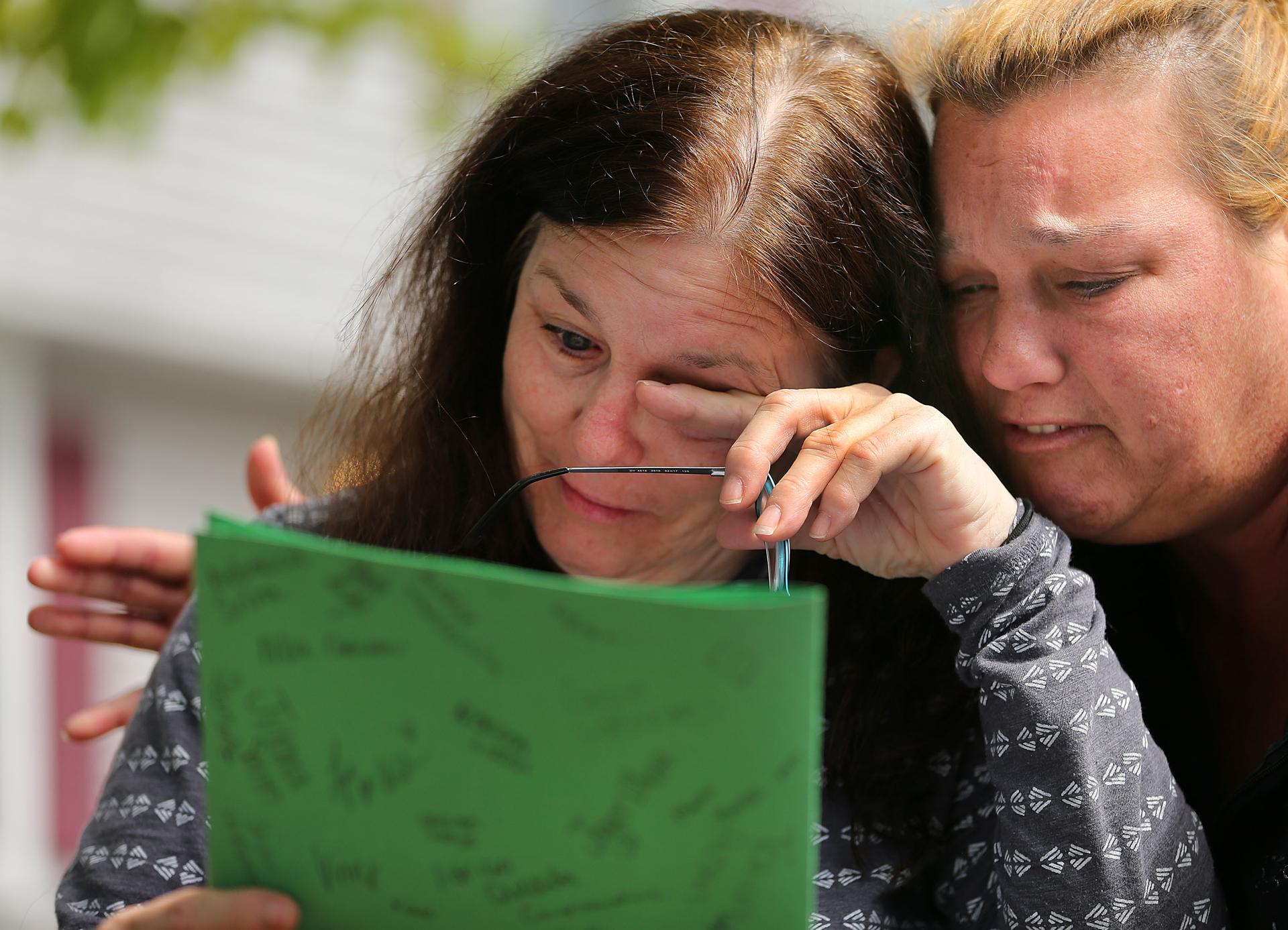 Jeanne Doyle (left) was comforted by a friend as she read a signed card from students at Rogers Middle School.