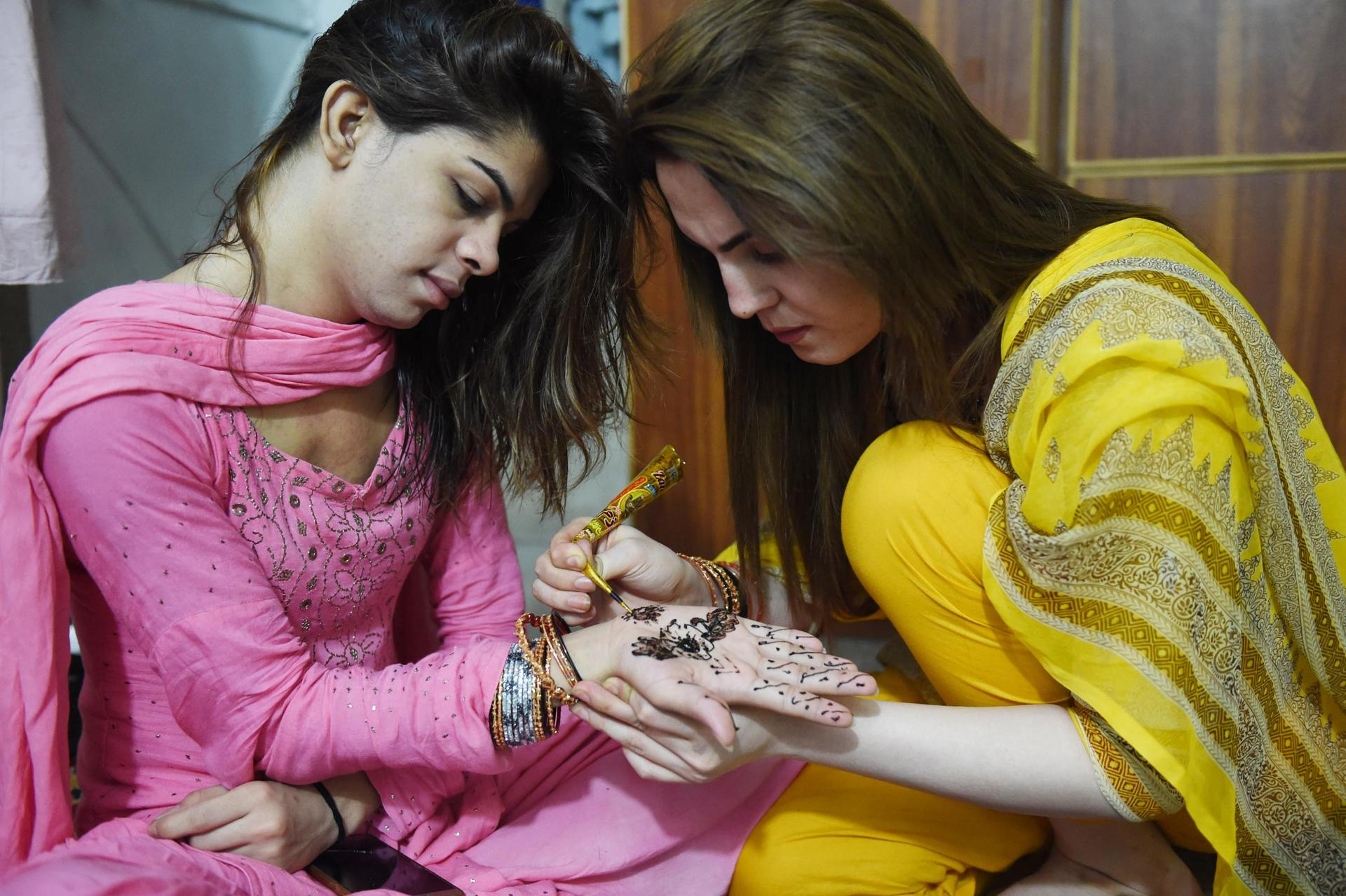 Pakistani transgenders decorate hands with henna ahead of the Eid al-Fitr festival in Peshawar on July 5, 2016. Millions of Muslims around the world prepare to celebrate the Eid al-Fitr feast marking the end of the fasting month of Ramadan. / AFP PHOTO / A MAJEEDA MAJEED/AFP/Getty Images