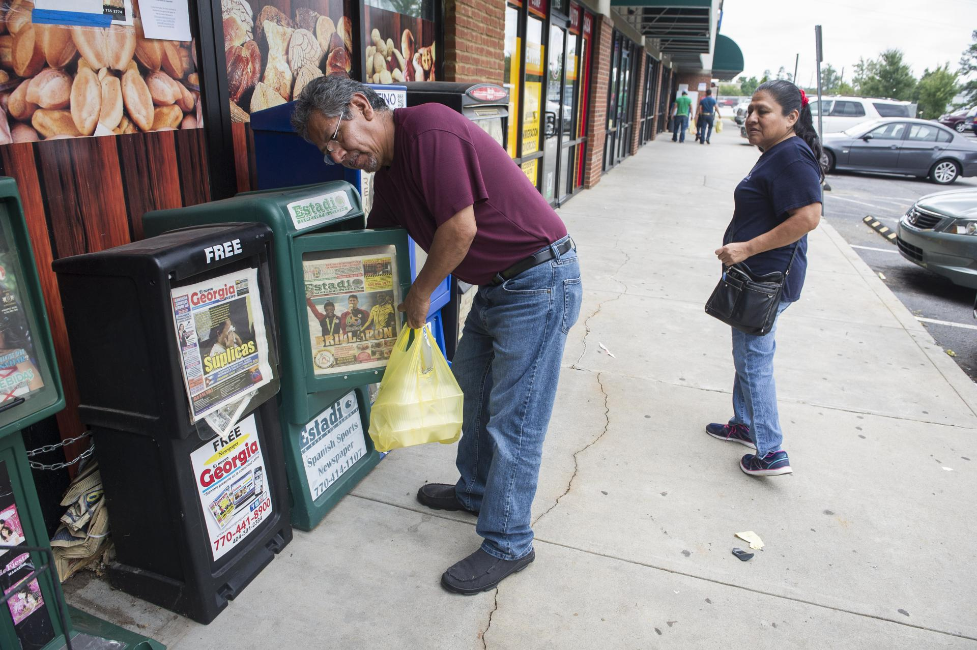 Roberto Gonzalez, Of Mexico, Gets A A Newspaper Out Of Boxes Catering To  The Hispanic