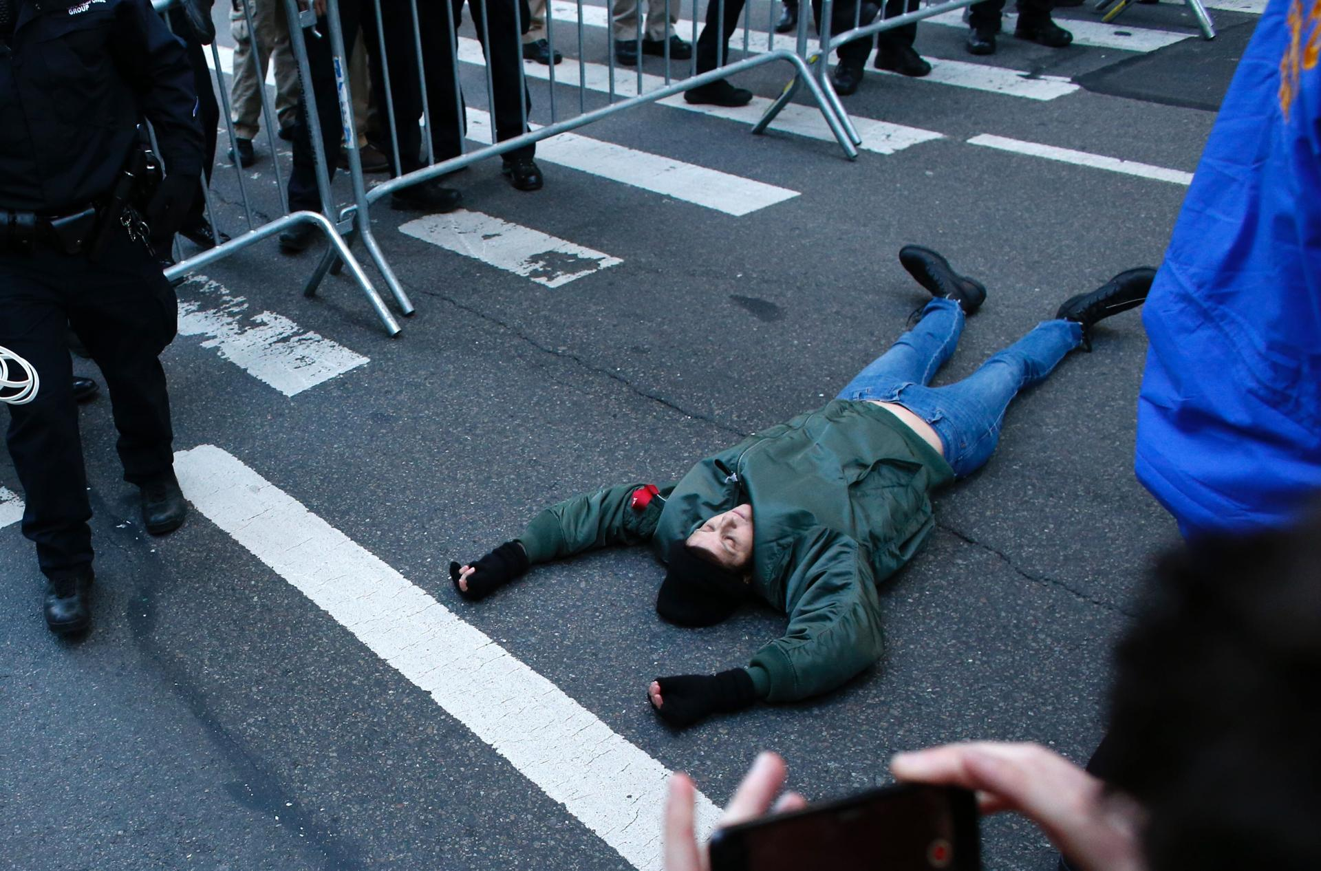 A woman laid down on the street after she jumped the fence during a protest againts US President-elect Donald Trump in front of Trump Tower on Saturday.