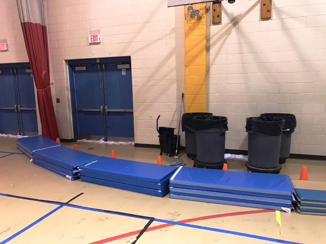 In the gym at at the Pine Grove Schoo​l in Rowley: Barrels to catch rain leaking from the roof, cones and mats to keep students away from the water, and towels along the bottom of the outside doors to keep water from leaking in. (handout)