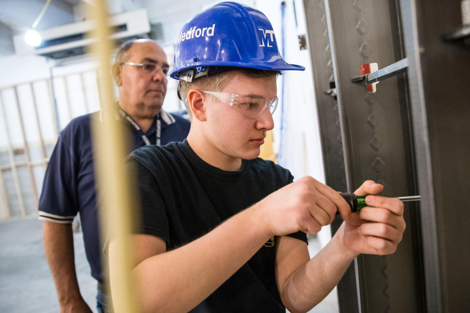 05/08/2017 MEDFORD, MA Electrical teacher Rich Cormio (cq) (left) watches as Matt Grant (cq) 16, installs an outlet at Medford Vocational Technical High School. (Aram Boghosian for The Boston Globe)
