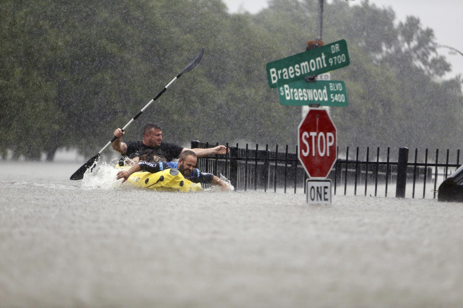 Two kayakers try to beat the current pushing them down an overflowing Brays Bayou along S