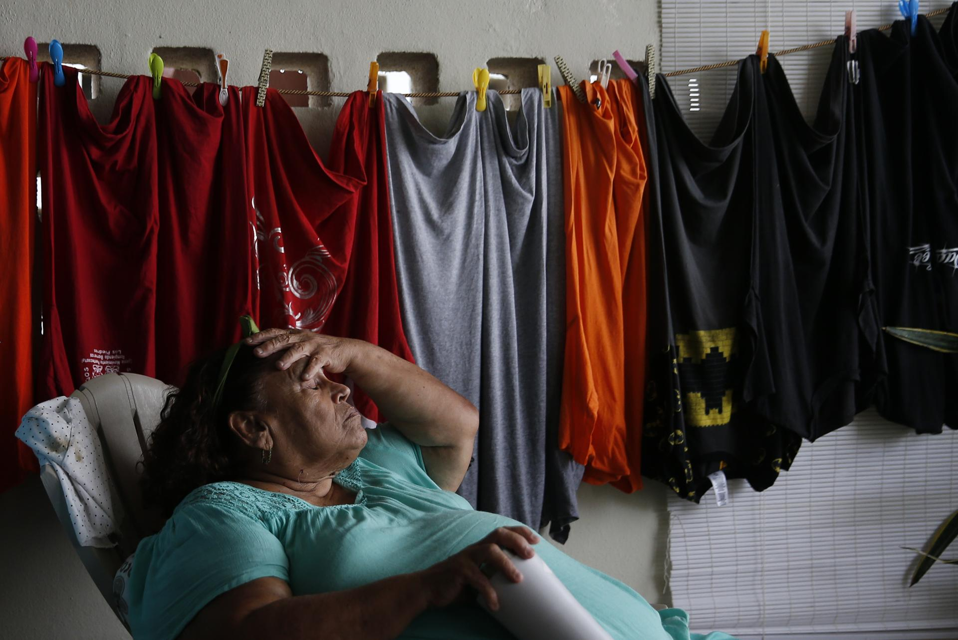 Carmen Charriez, 71, has slept in this chair in her garage since Hurricane Maria hit and severely damaged her home.