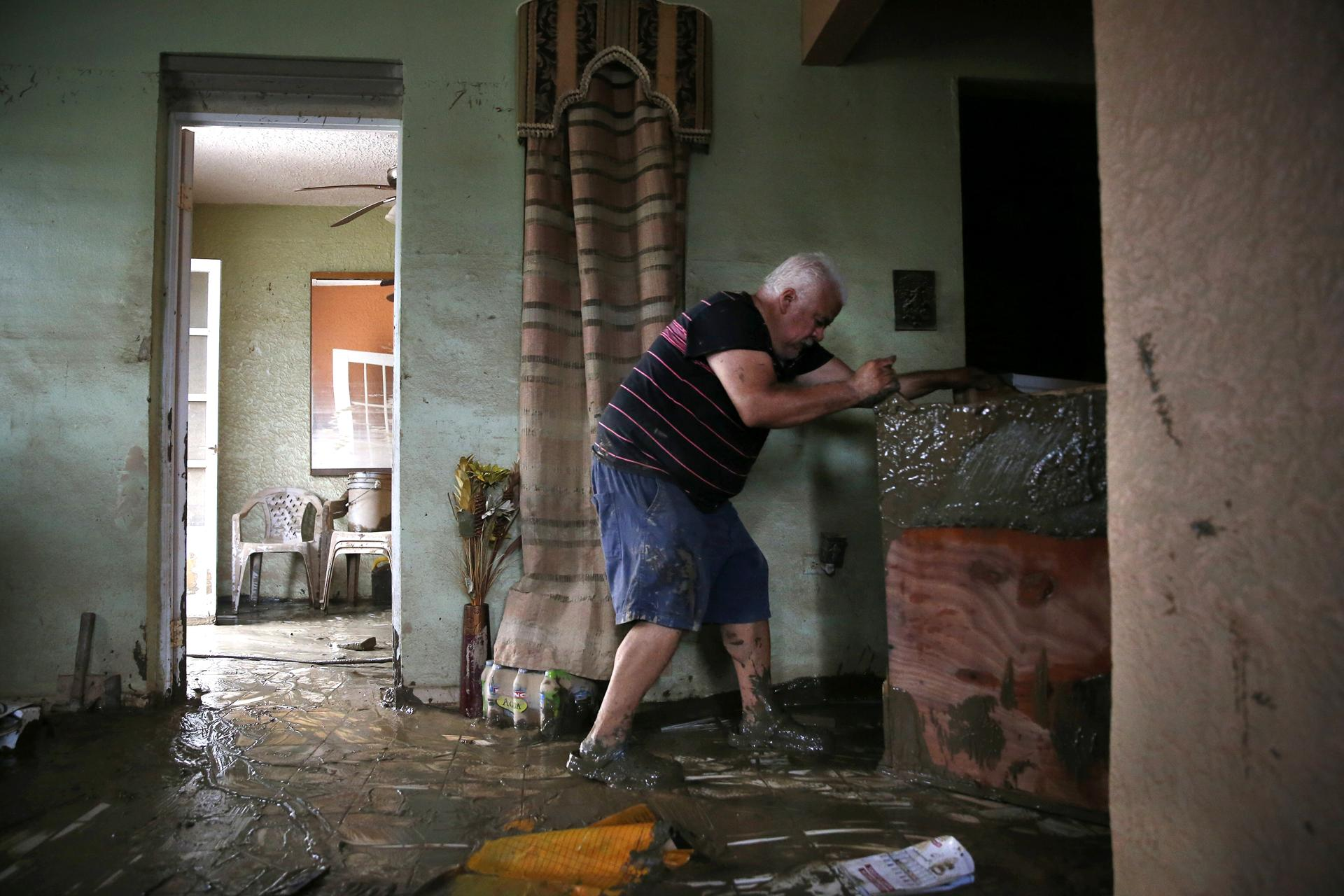 Toa Baja, Puerto Rico -- 9/30/2017 - Geraldo Rivera, 51, helps his neighbor move a dresser ruined in the flood waters inside the home on Avenida Calle Palma Villa Calma after Hurricane Maria. (Jessica Rinaldi/Globe Staff) Topic: Reporter: