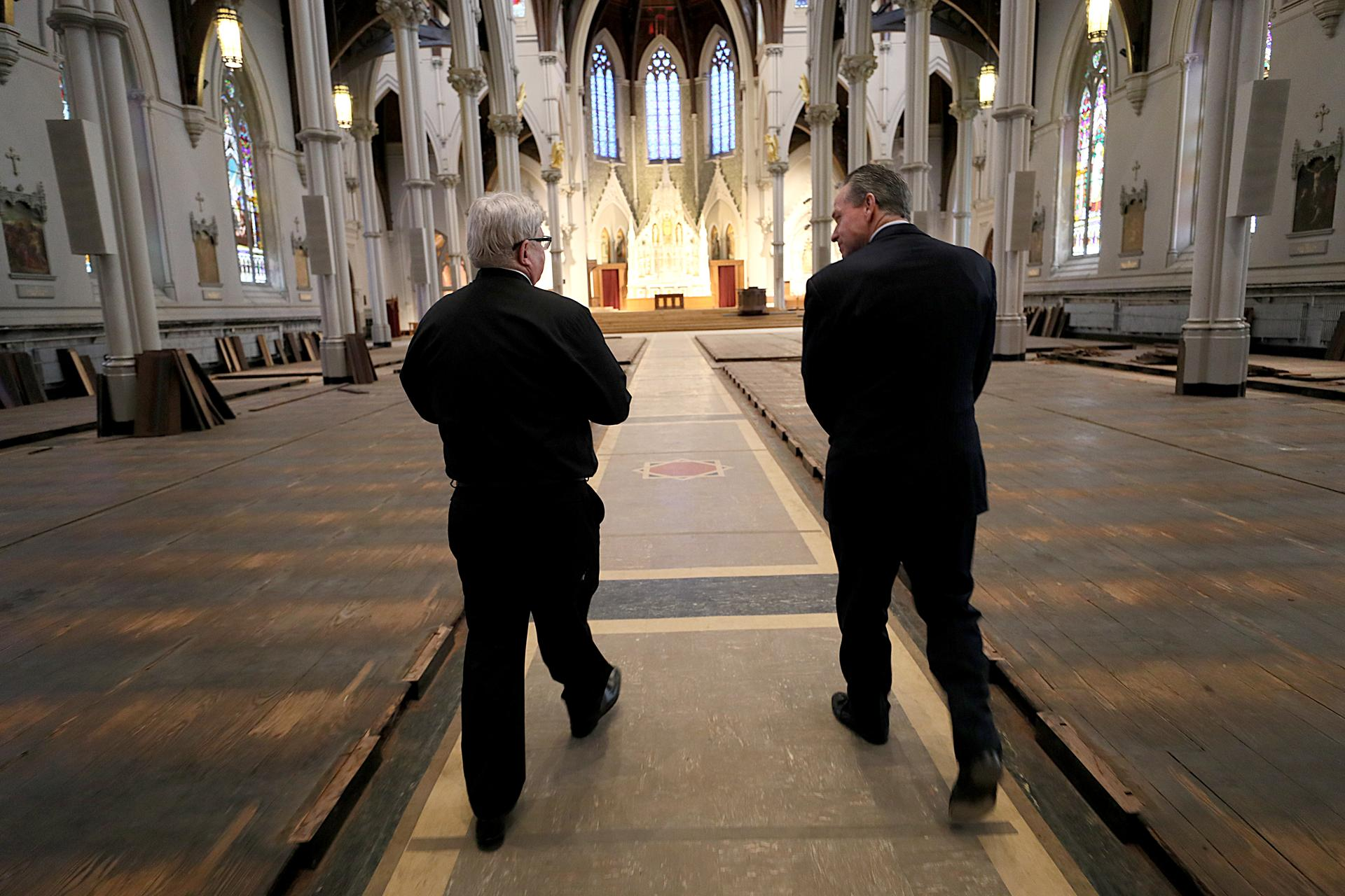 Father Kevin O'Leary (left) and John Fish of Suffolk Construction walked through the Cathedral of the Holy Cross in Boston.