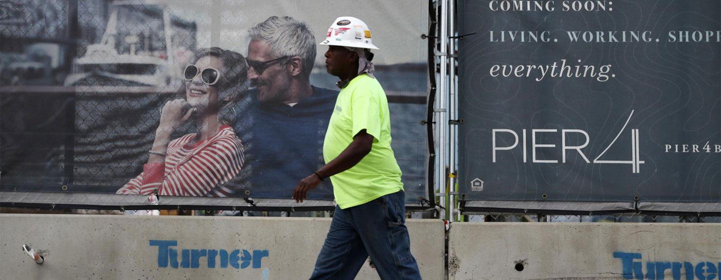 Laborer Randall Turner walked past an advertisement for the Pier 4 development on Northern Avenue.