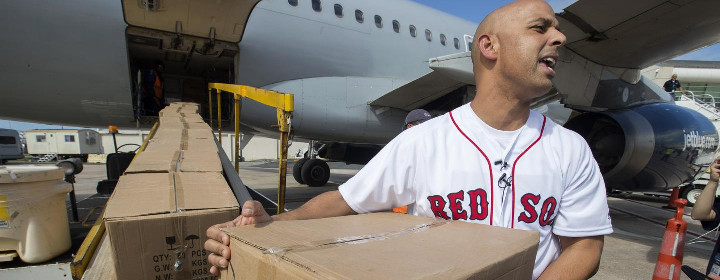 Alex Cora unloads some of the 10 tons of relief supplies sent to his native Puerto Rico.