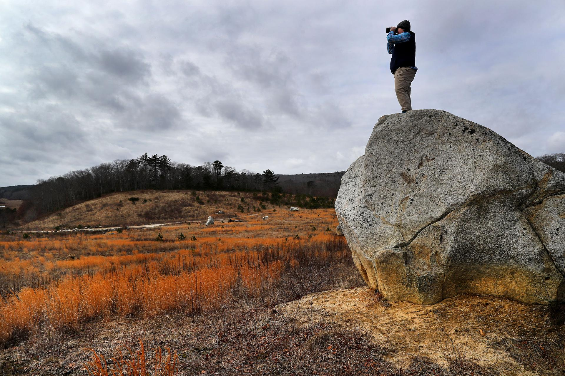 PLymouth-02/14/18 Lauren Kras, a wildlife bioligist stands on a huge rock looming over the sand plain below, which once was a big gravel pit used at the former cranberry bogs at the newly opened 450-plus acre Mass Audubon's Tidmarsh Wildlife Sanctuary. The former working cranberry farm underwent the largest freshwater ecological restoration ever completed in the Northeast. Slowly, new wildlife is attracted to the three and a half miles of landscape that was created by removing nine dams to reconnet the headwaters of the Beaver Dam Brook to the ocean. John Tlumacki/Globe Staff(metro)