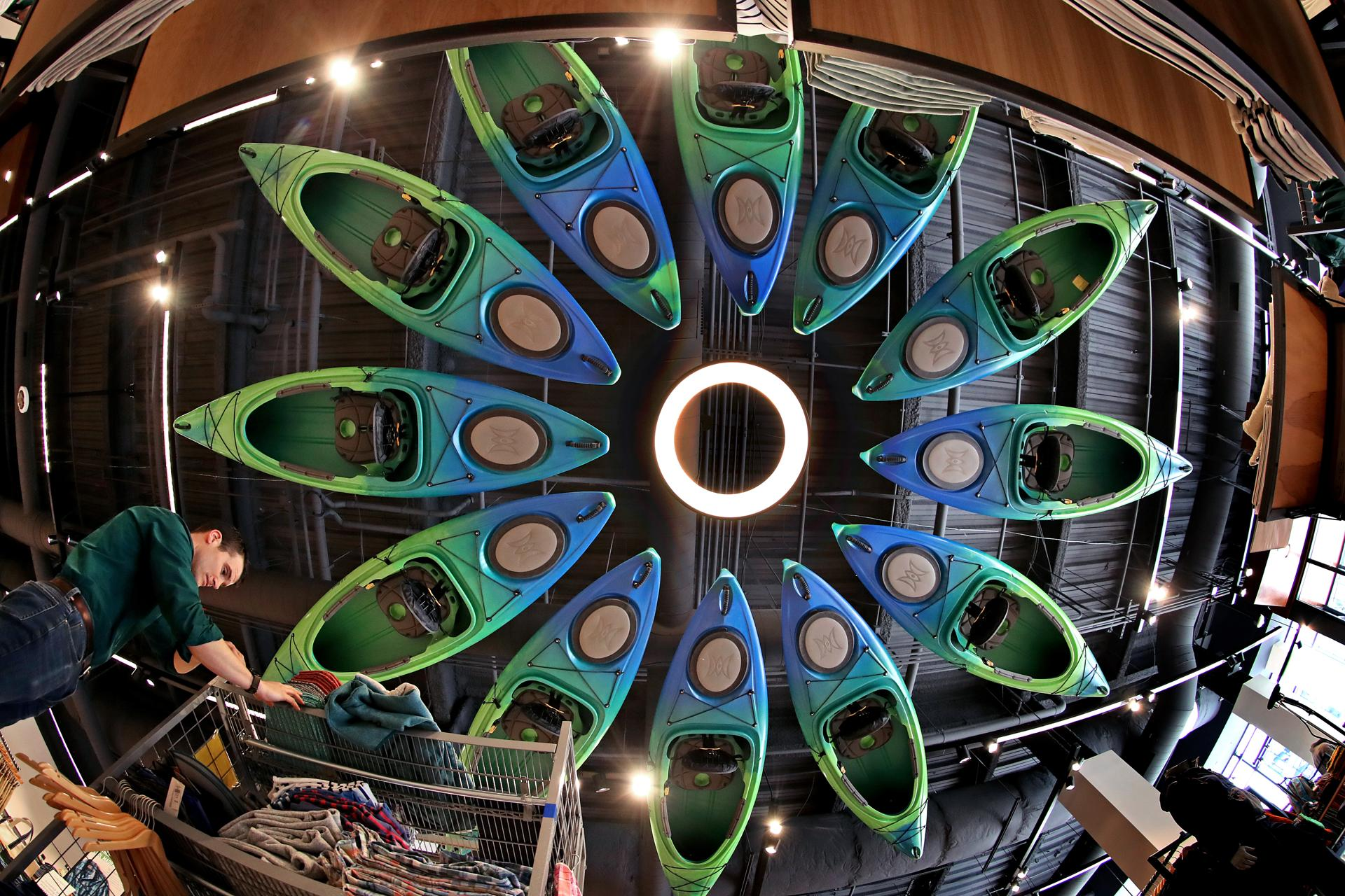 BOSTON, MA - 3/27/2018: Kayaks are hung in the ceiling of the store for decoration as employee Greg Dorman works with setting up merchandise. L. L. Bean comes to the Seaport District in Boston which will open April 6th. (David L Ryan/Globe Staff ) SECTION: BUSINESS TOPIC