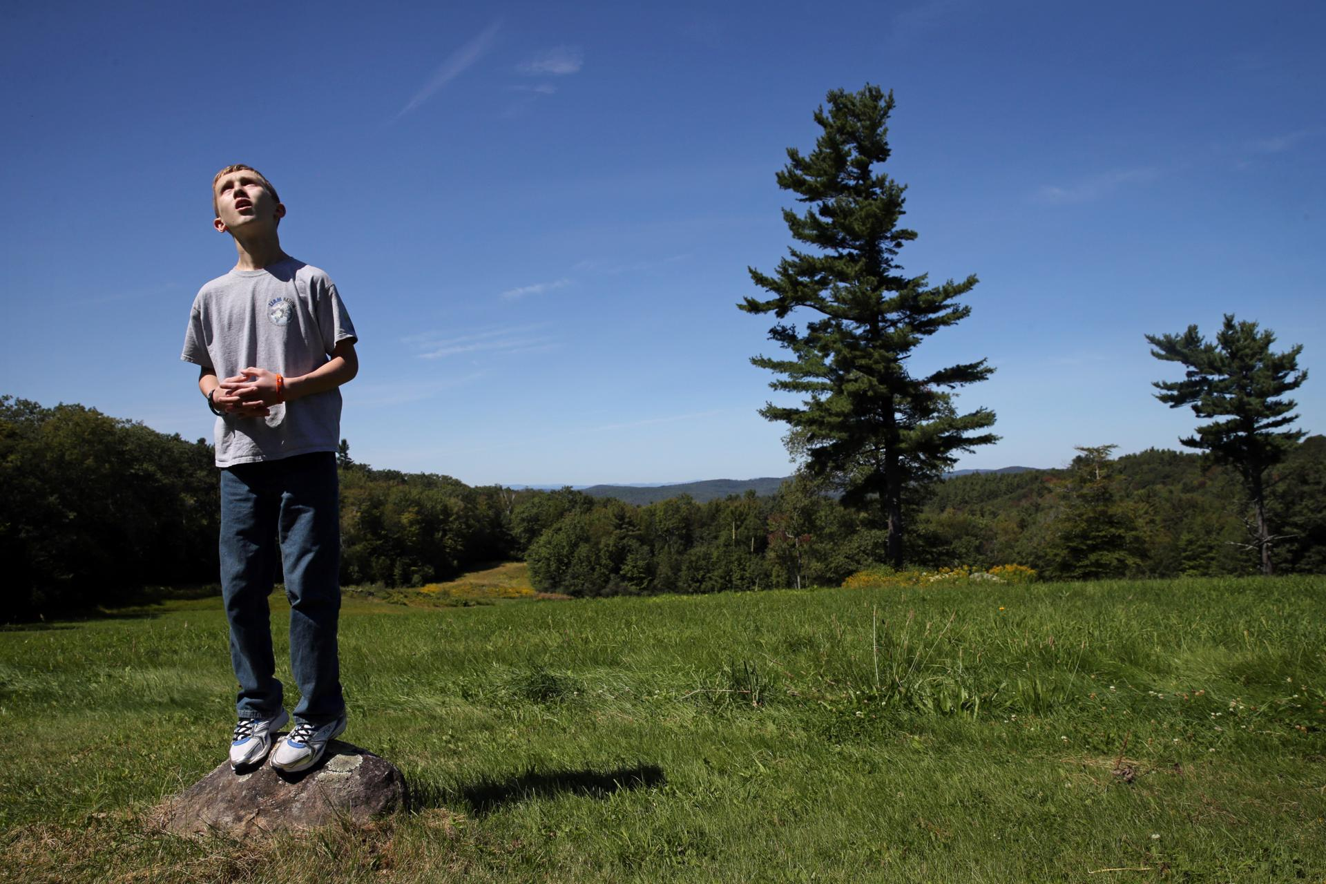 Nelson, NH- September 02, 2017: Connor Biscan stood atop a small rock and searched the sky for the balloons he had lost at a family gathering in Nelson, N.H., on Labor Day weekend last September. Connor had flown the balloons in an open field behind his great-grandfather's house. When the kite string broke and the balloons snagged on a tree, Connor became anxious. His mother, Roberta Biscan, praised him for remaining calm. As a baby, balloon was his first word. (Craig F. Walker/Globe Staff) section: metro reporter: kowalczyk