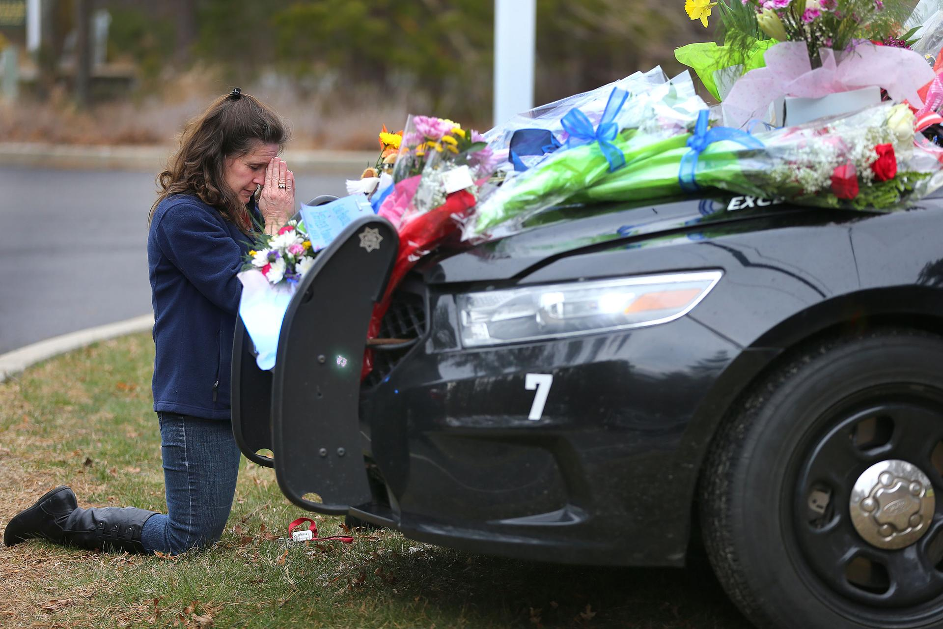Jeanette Smith from Harwich knelt and prayed in front of the cruiser belonging to slain Yarmouth k-9 officer Sean Gannon which is adorned with flowers parked in front of the police station.