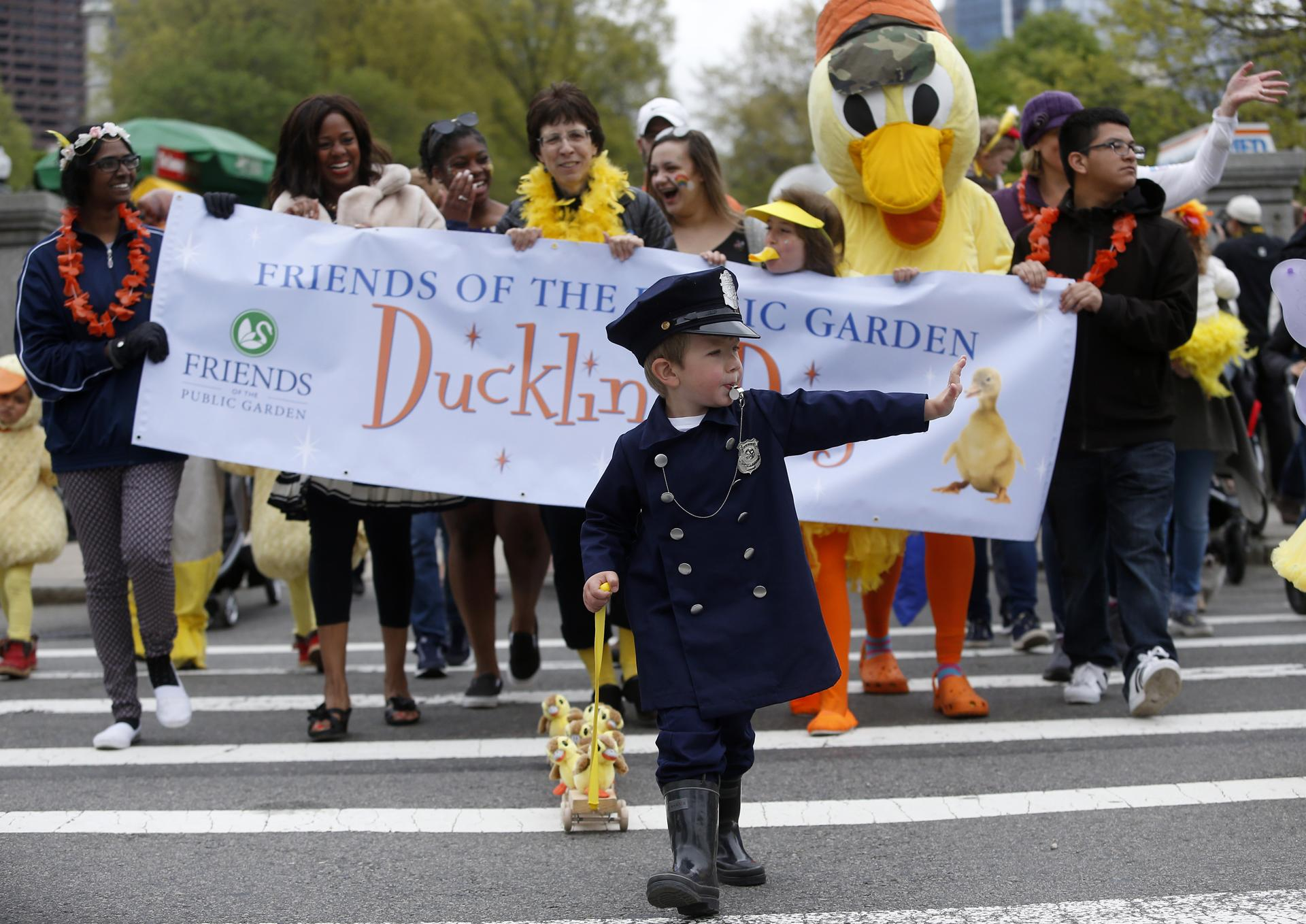 "Jonathan Krygowski, 4, of Westford, blew the whistle as he led the Duckling Day parade dressed as Michael from the children's story, ""Make Way for Ducklings."""