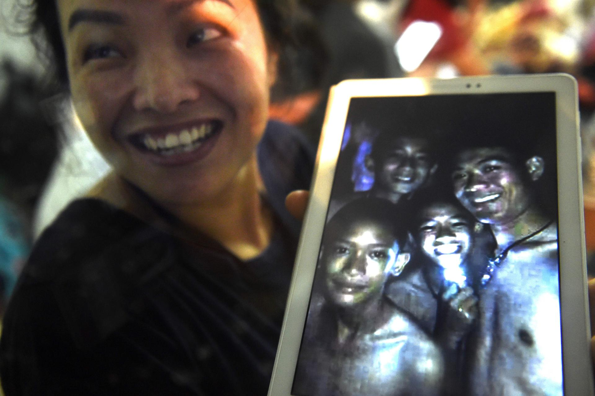 A happy family member showed photographers the latest picture of the missing boys taken by rescue divers.