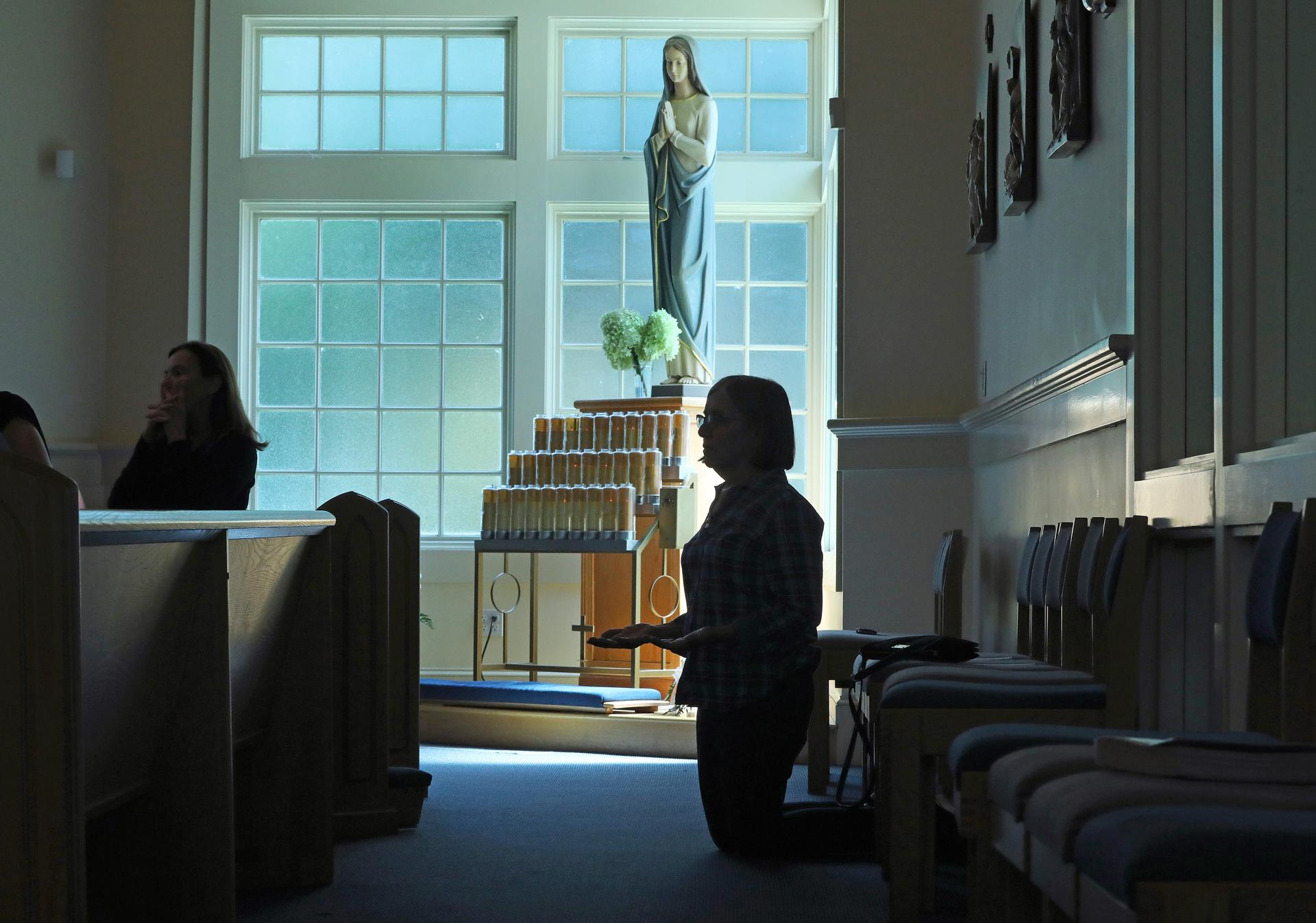 ********************** DO NOT LIGHTEN ******************************* DO NOT LIGHTEN ****************************** DO NOT LIGHTEN **************** Hanson, MA - 9/2/18 - Catherine Dicker (cq), a member of this church's sister parish, kneels in prayer, in the rear. Father Michael Hobson (cq) celebrates Mass in St. Joseph the Worker Parish, as local Catholics deal with the current upheaval over cover-ups of sex crimes in the church. Photo by Pat Greenhouse/Globe Staff Topic: 09catholics Reporter: Jenna Russell