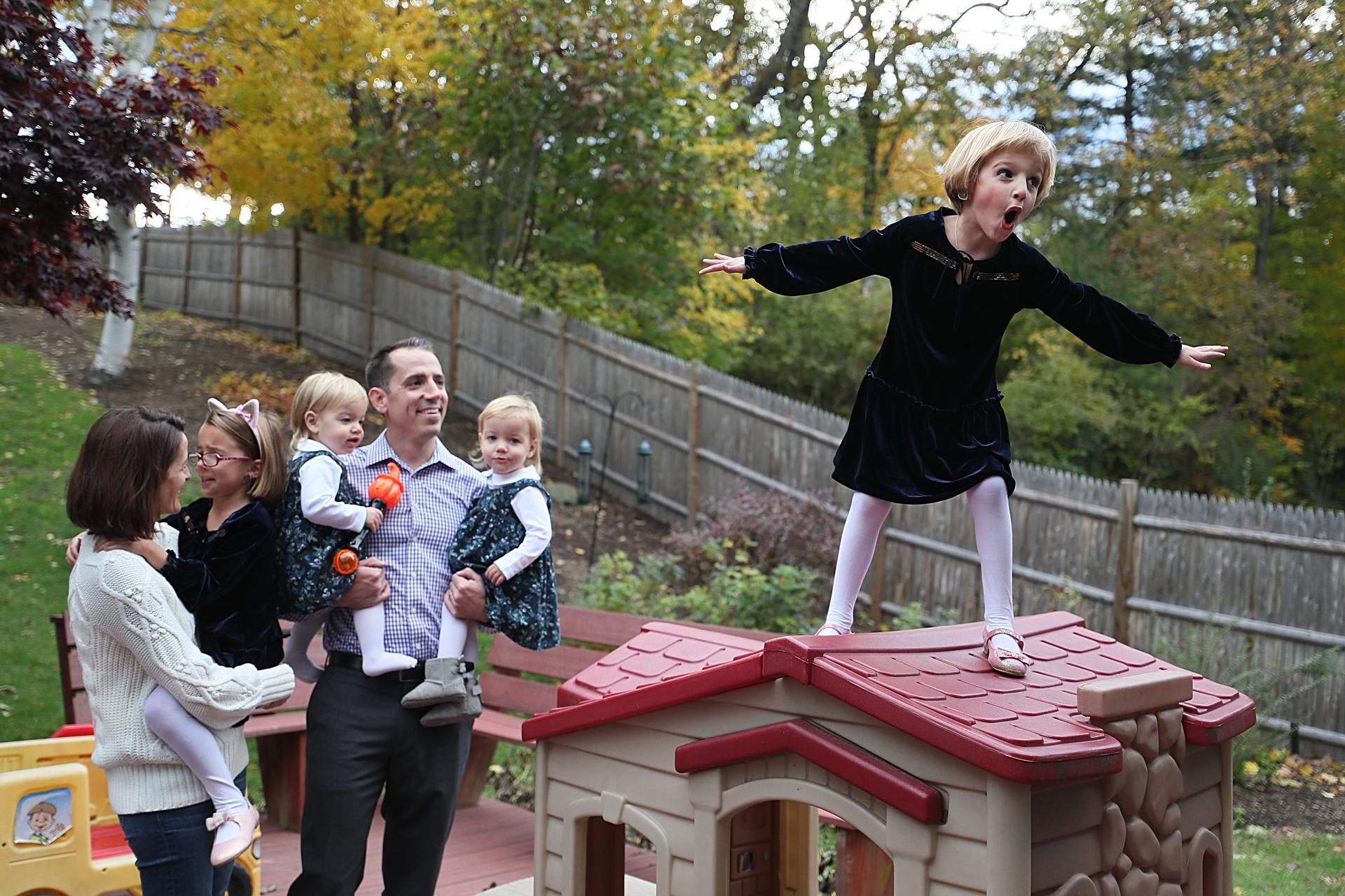 Needham, Ma., 10/30/2018, This is the d'Hemecourt family, whose 5-year-old Michaela, on roof of playhouse, recently came out as transgender. The family hosted a block party to break the news and to ask their neighbors to support them in the campaign for Question 3, the ballot question that deals with transgender rights. Left to right: Liza, Elizabeth, 6, twins Winnie and Violet, 20 months, and Dad is Michael. Suzanne Kreiter/Globe staff