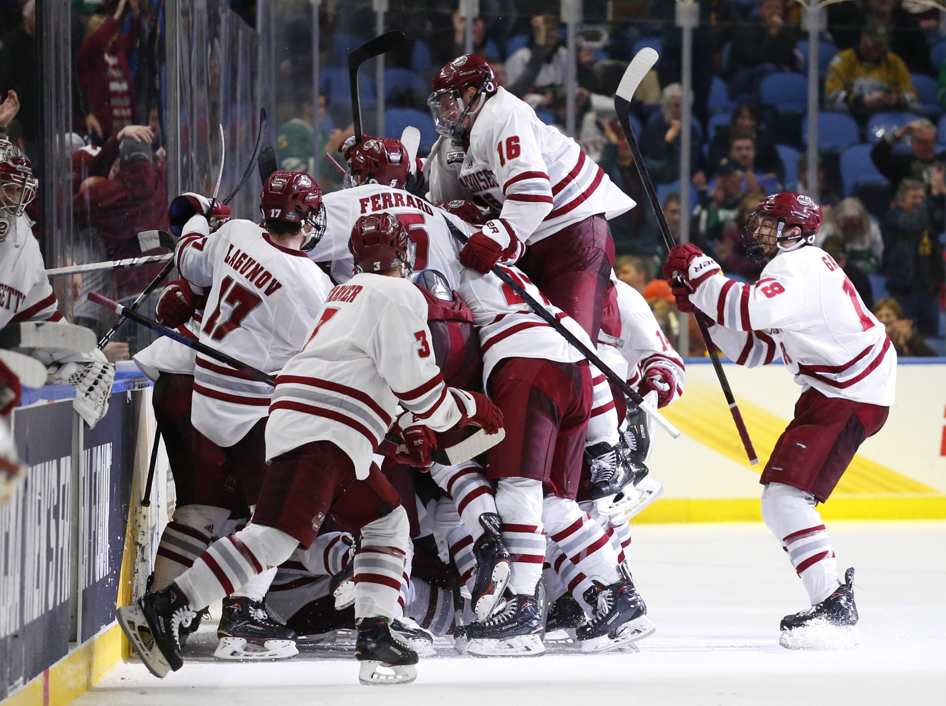 Massachusetts players celebrate a 4-3 overtime victory over Denver in the semifinals of the Frozen Four NCAA men's college hockey tournament Thursday, April 11, 2019, in Buffalo, N.Y. (AP Photo/Jeffrey T. Barnes)