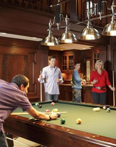 TAKING THEIR CUES The Renner family's home in Weston has a mahogany-clad billiard room, designed by Foley Fiore, situated in the heart of the house.