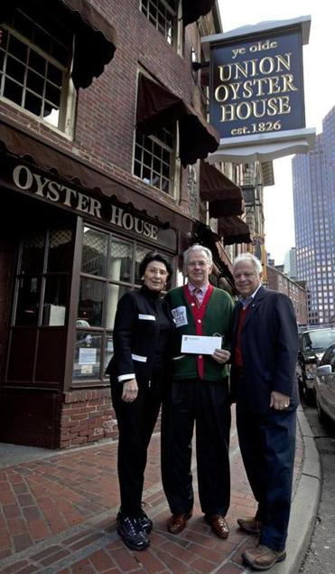 Mary Ann Milano-Picardi and Joe Milano, co-owners of Ye Olde Union Oyster House in Boston, presented William Connolly with a $5,000 check for Globe Santa.