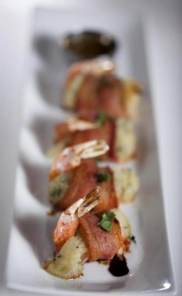 Shrimp with yuca are wrapped in bacon.
