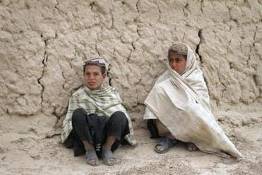 Boys sat in Panjwai, Afghanistan, near where at least 16 civilians were methodically killed and some of their bodies were burned.