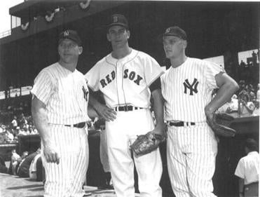 Mickey Mantle, Don Schwall, and Roger Maris along the first-base dugout.