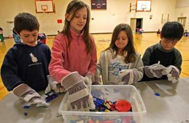 "Sharon third-graders (from left) PJ McManus, Eva Wallace, Amelia Scappaticci, and Allen Zhang try their hand at a dexterity activity with Lego bricks while wearing ""space gloves.''"