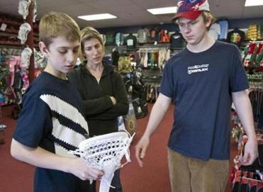 Nolan Holbrook, 13, with his mother, Shannon, checked out a lacrosse stick with salesman Chris Mackay at Comlax.