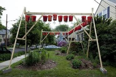 Eli Katzoff's tomato-growing front-yard display in Newton looks like an oversize swing set, stretching 13 feet high, with 34 red hanging buckets of tomato plants resembling a string of Chinese lanterns from afar.