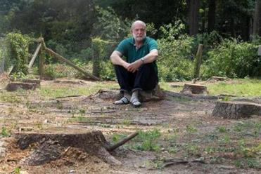 Richard Salus sits on one of 22 pine tree stumps behind his residence which were cut down by Ntar.