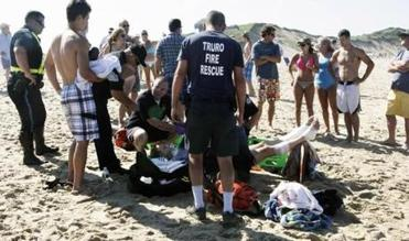 JJ Myers, in plaid trunks, looked on as paramedics tended to his father, Chris, on Truro's Ballston Beach in July 2012.