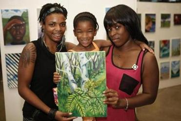 Artist Kitauna Parker (left) posed with her painting and her mentor Cassandra Lattimore (right) and her daughter, Justice Lattimore-Wellington at the Artists for Humanity's End of Summer exhibitio,..