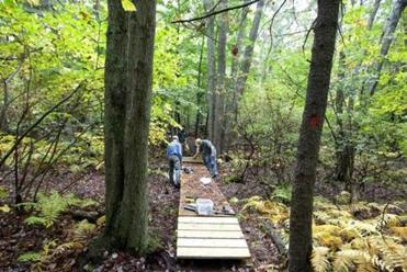 Trustees of Reservations employees and volunteers met at the Noon Hill trail in Medfield, Massachusetts where they completed the construction of a foot bridge.