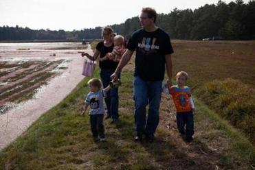 Luke and Jessie Donoho, with sons Zendon (right), Blaise, and baby Niall, take a walk around the A.D. Makepeace bogs during the Cranberry Harvest Celebration in Wareham.