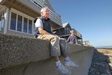 Richard and Judy Wainwright sat on the seawall by their Scituate oceanfront home awaiting Hurricane Sandy.